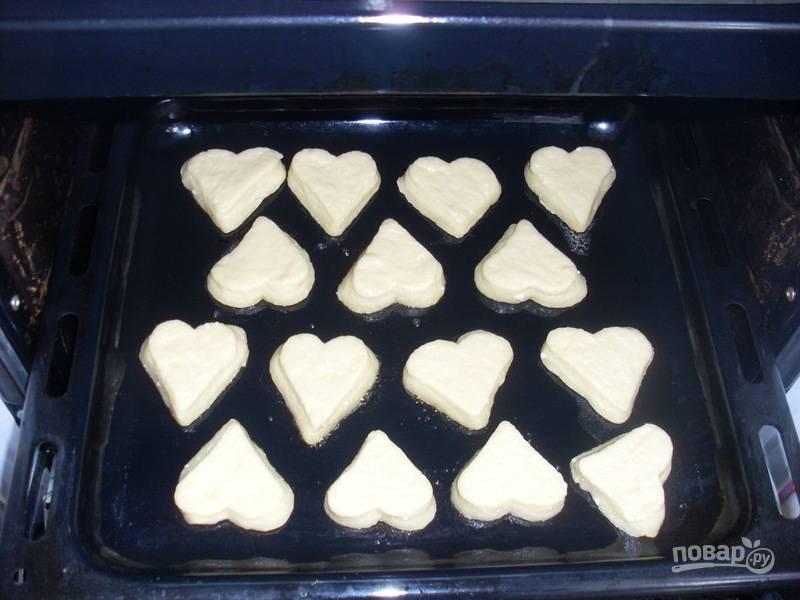 Раскатайте готовое тесто толщиной в 1-1,5 см. Вырежьте печенья. Переложите их на противень, немного смазанный маргарином или маслом.