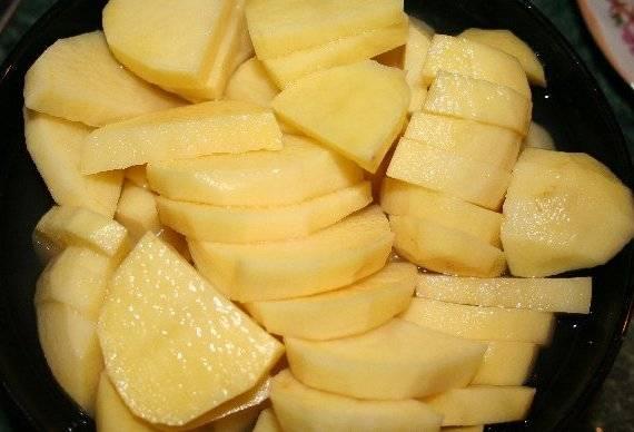 Пока говядина тушится, мы чистим картофель и нарезаем его ломтиками.