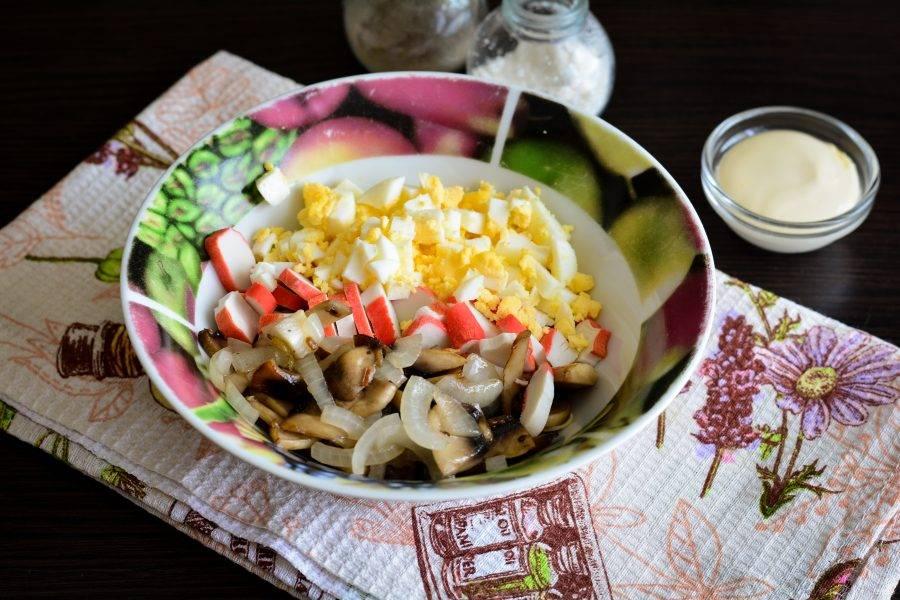 В плошке соедините яйца, крабовые палочки и жареные грибы с луком. Добавьте по вкусу соль и черный перец.