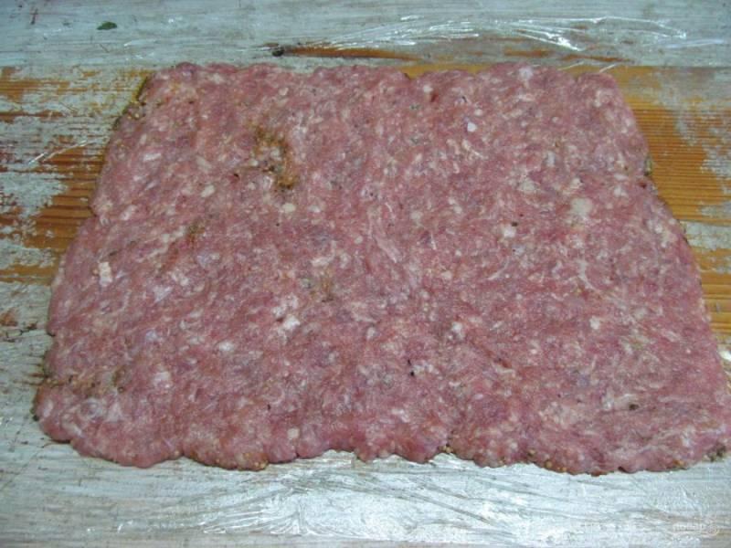 На специи выложите тонким слоем свиной фарш, лучше это делать мокрыми руками. Сформируйте ровный прямоугольник.