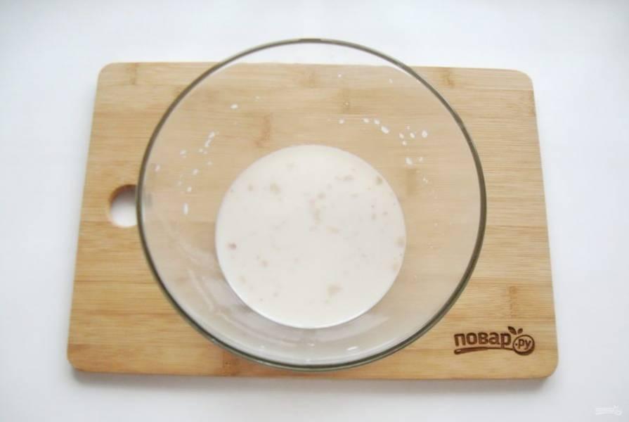 Приготовьте опару для теста. В миску налейте теплое молоко. Добавьте дрожжи, 2 столовые ложки муки и столовую ложку сахара.