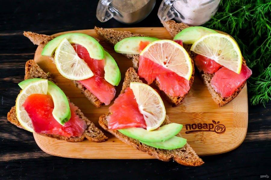 Авокадо очистите от кожуры, разрежьте пополам. Удалите косточку и нарежьте мякоть ломтиками, сбрызните лимонным соком. Выложите на бутерброды, посолите и поперчите их по вкусу.