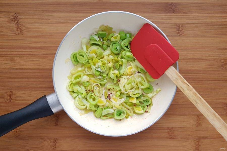 Лук порей нарежьте колечками. На сковороде распустите столовую ложку сливочного масла и пассеруйте порей до мягкости. В конце приготовления посолите и поперчите.