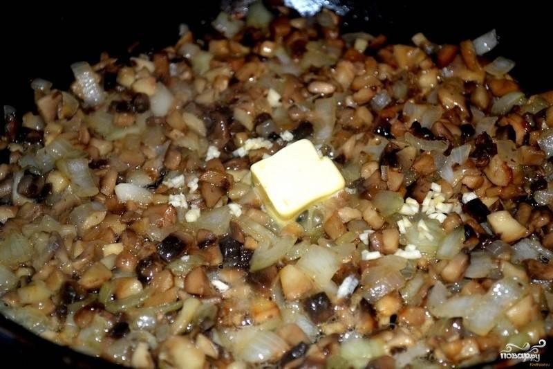 К луку добавьте грибы, в сковороду налейте несколько столовых ложек чистой воды. Протушите ингредиенты, пока не выпарится жидкость. Затем добавьте немного сливочного масла, раздавленный зубчик чеснока и дождитесь, когда на грибах появится золотистая корочка.