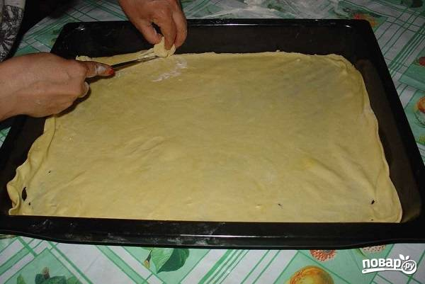 7. Теперь можно начинать собирать пахлаву. Один кусочек теста раскатайте тонко и выложите на противень, предварительно смазав его маслом или застелив пергаментом.