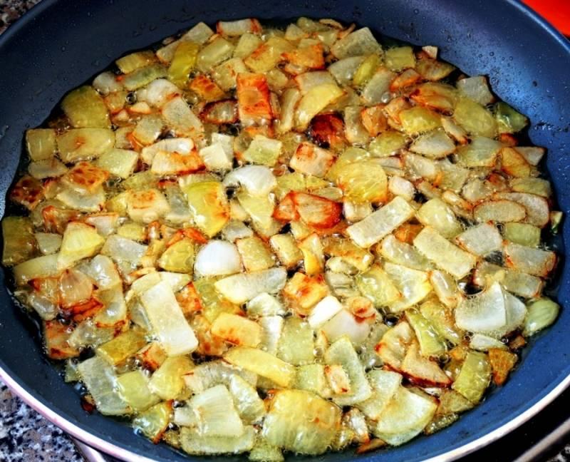 Тем временем порежьте и обжарьте лук. После жарки выньте лук из масла.