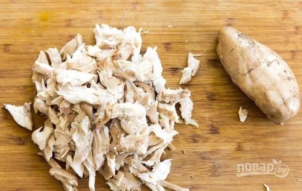 4. Куриное филе предварительно отварите, после чего настругайте ножом на средние кусочки.