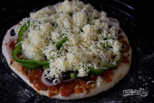 На присыпанном мукой столе раскатайте тесто, смажьте пласт маслом и выложите томатный соус. Выложите начинку и натертый сыр.