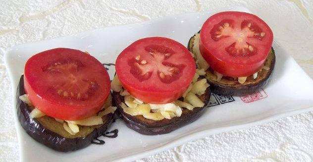 Помытые и нарезанные кружочками помидоры выложите на сыр.