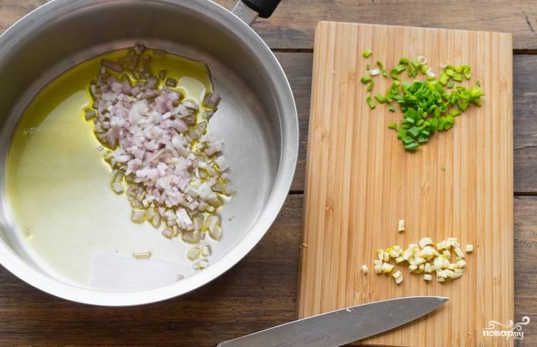 В оливковом масле обжариваем лук-шалот. Тем временем измельчаем чеснок и зеленый лук.