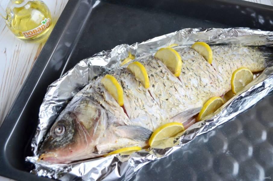 5. Делаем из фольги лодочку, я использовала два слоя плотной фольги, чтобы сок рыбный не вытекал. Сделайте надрезы, вставьте дольки лимонные, вокруг тоже положите лимончик. Отправьте в горячую духовку (200 градусов) на 20-30 минут, в зависимости от размера рыбы.