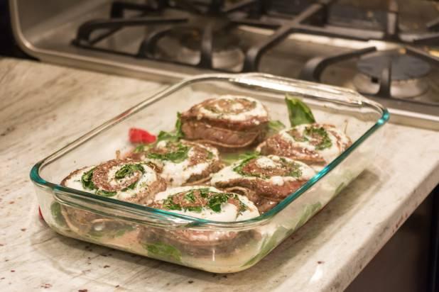 8. На дно формы для запекания можно выложить шпинат, который потом будет подан в качестве гарнира, например. Отправляем мясо в разогретую духовку и запекаем до готовности около 35-50 минут (в зависимости от толщины кусочков).