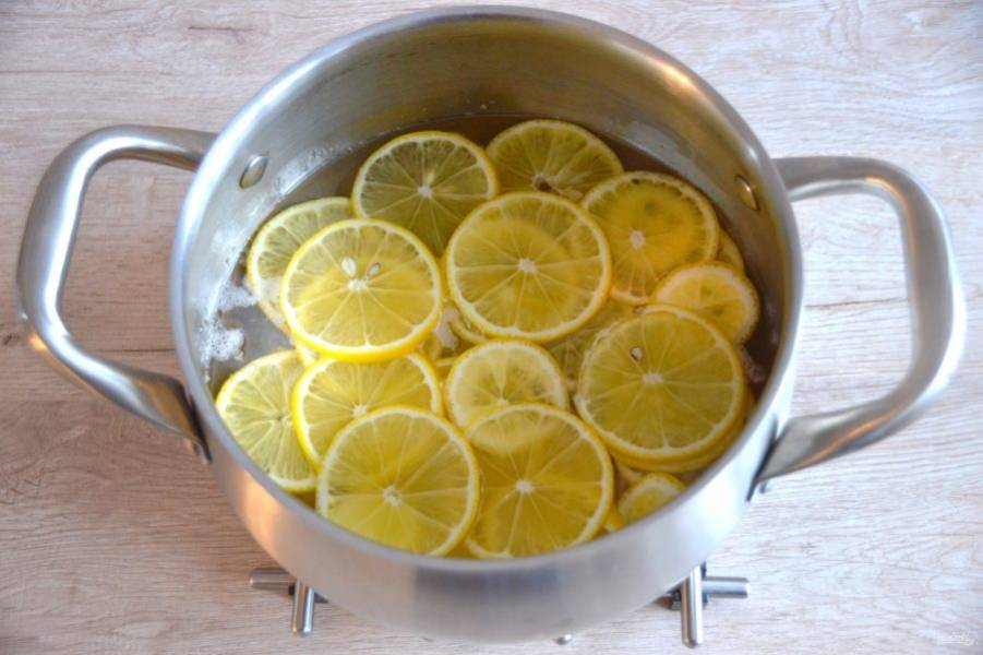 Выложите лимонные ломтики в сироп, понизьте температуру нагревания и проварите 30 минут (без кипения) на медленном огне.