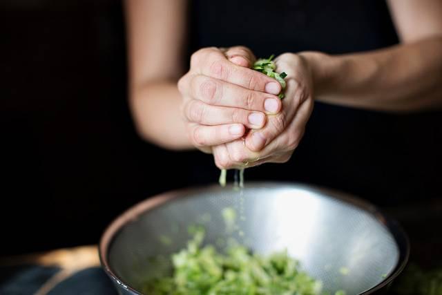 3. Параллельно очистите луковицу и чеснок (если готовите для детей, их можно не использовать). На сковороде разогрейте немного растительного масла, отправьте туда лук с чесноком. Обжарьте немного на среднем огне. Кабачки тем временем отожмите, чтобы удалить лишнюю воду.