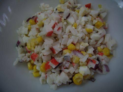 Смешать яйца, крабовые палочки,кукурузу, рис, лук. Заправить майонезом и выложить горочкой на тарелку.