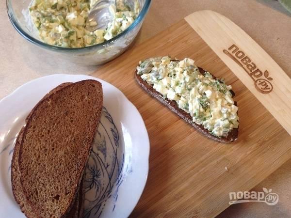 7. Ломтики черного хлеба подсушим в тостере и выложим на них салат.