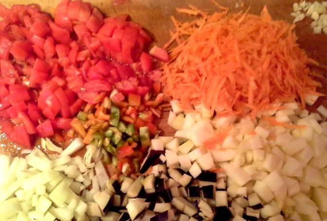 Нарезаем овощи. Лук, баклажаны, помидоры и перец режем частично кубиками, частично полукольцами. Морковь можно просто натереть на терке.