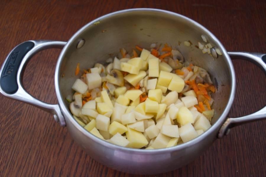 Добавьте очищенный и нарезанный кубиком картофель. Перемешайте. Залейте водой и поставьте вариться.