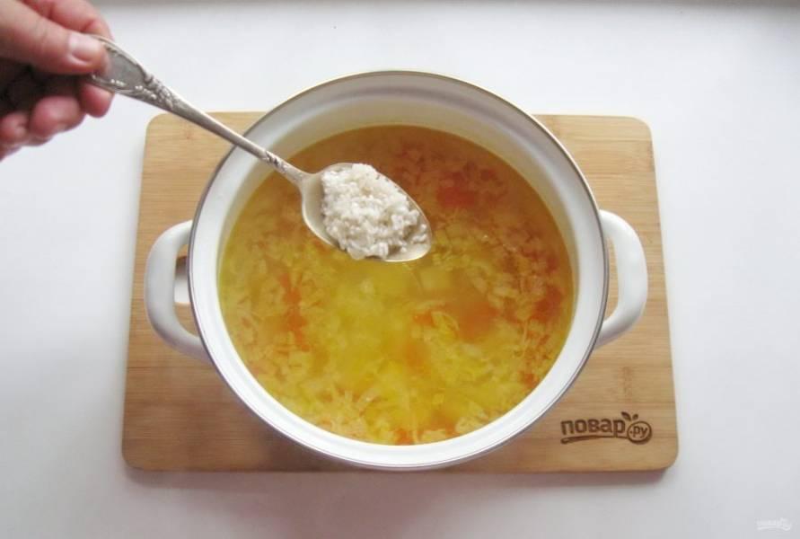 Выложите в кастрюлю морковь и лук. Проварите овощи 10-15 минут и всыпьте рис, который следует тщательно помыть.