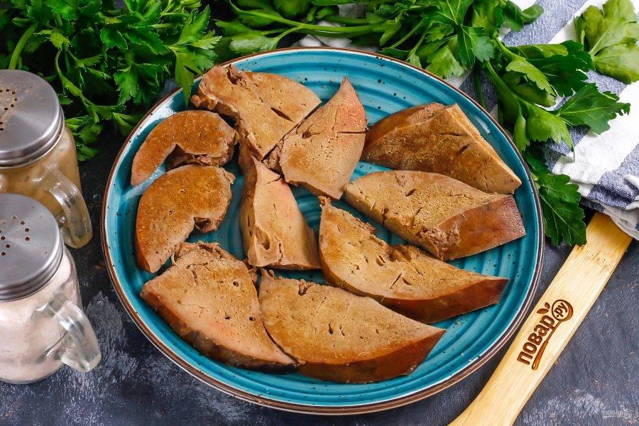 Извлеките печенку из бульона и нарежьте ее порционными ломтиками, выложите их на тарелку. Тарелку по желанию можно застелить салатными листьями.
