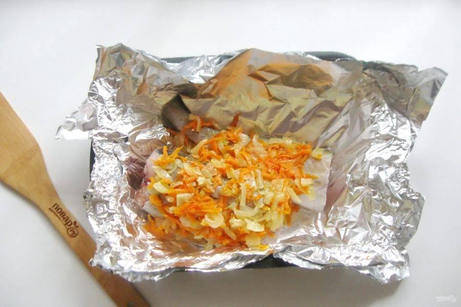 На минтай выложите лук с морковью, которые тушились в сковороде. Заверните плотно в фольгу рыбу с овощами.