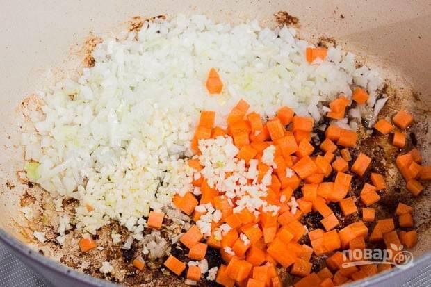 4.Нарежьте мелко лук и чеснок, мелким кубиком нарежьте морковь. Выложите овощи в казанок и обжарьте до мягкости, соскребите любые корки со дна казанка, что остались после мяса (это важно!).