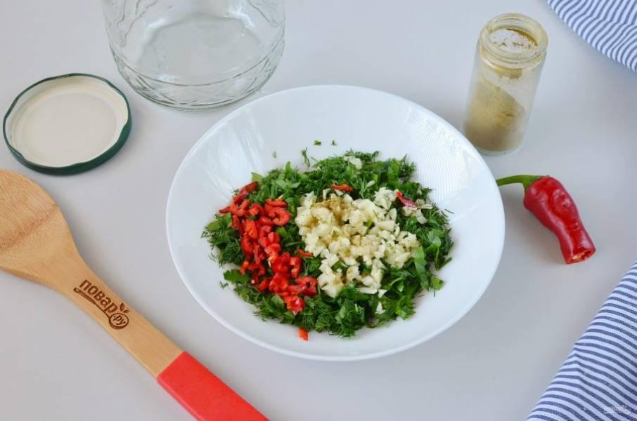 Порежьте мелко петрушку, укроп, чеснок и острый перец. Добавьте хмели-сунели и хорошо перемешайте массу.
