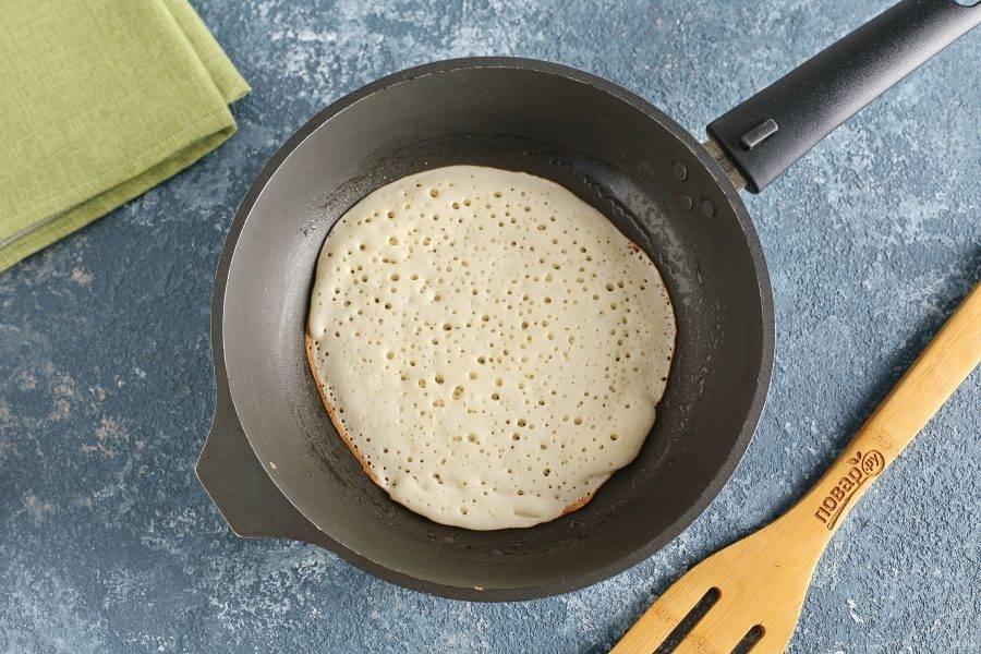 Разогрейте хорошо сковороду и смажьте ее растительным маслом. Выкладывайте блинное тесто небольшими порциями, равномерно распределяя по всей сковороде (диаметр может быть любой).