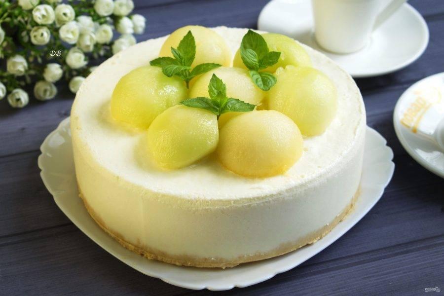 Перед подачей аккуратно снимите разъемную форму, сервируйте торт на блюдо. Украсьте поверхность торта полусферами из дыни и свежими листьями мяты (или базилика).