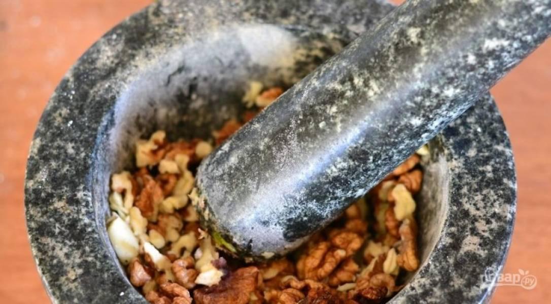 В ступке измельчаем чеснок и грецкие орехи до однородной массы.