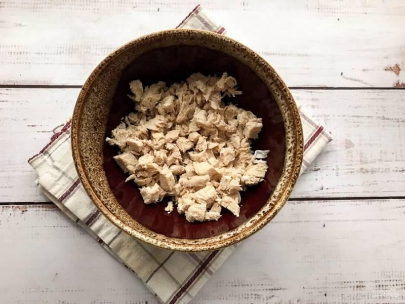 Вареную куриную грудку остудите, нарежьте небольшими кусочками и выложите в глубокую тарелку.