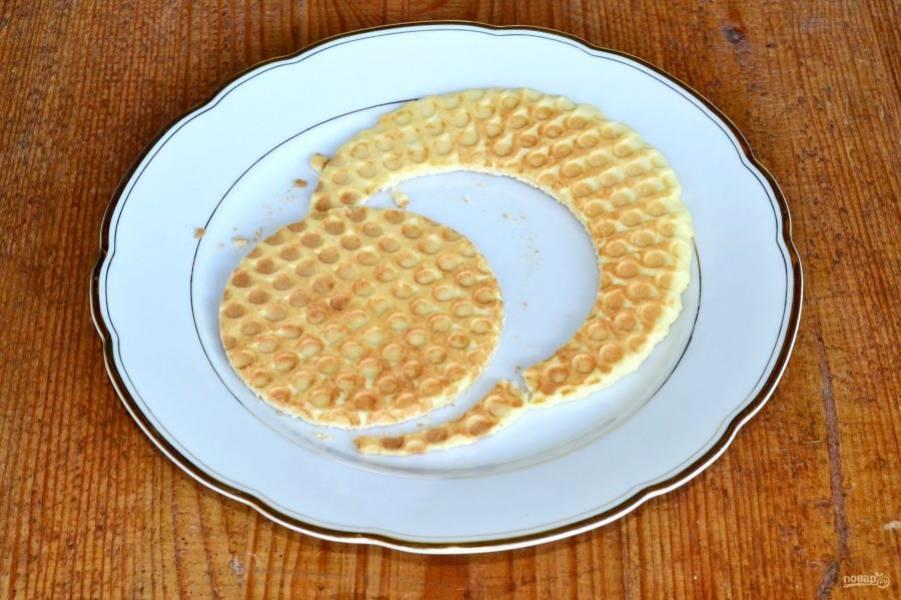 Пока вафля теплая, аккуратно подровняйте, чтобы получился ровный круг.