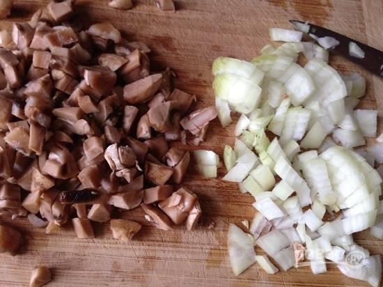 В первую очередь приготовим начинку для корзиночек. Грибы и лук нарезаем маленькими кубиками. Обжариваем минуты 3 лук, затем добавляем грибы и жарим минут 10, пусть выпарится жидкость.