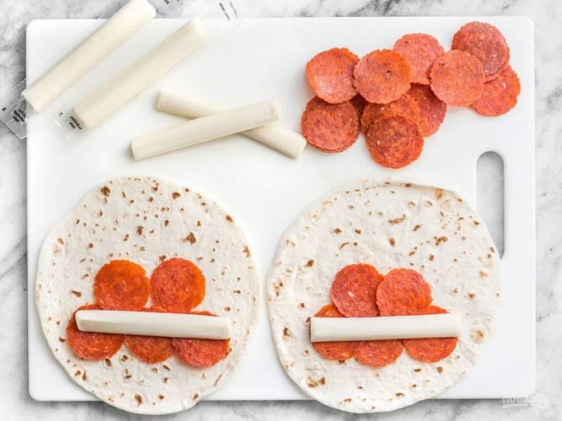 1.На поддон для микроволновой печи выложите лепешки, накройте влажным полотенцем и отправьте на 30-40 секунд в микроволновую печь. На каждую лепешку ближе к краю выложите внахлест по 5 ломтиков колбасы, добавьте палочку моцареллы.