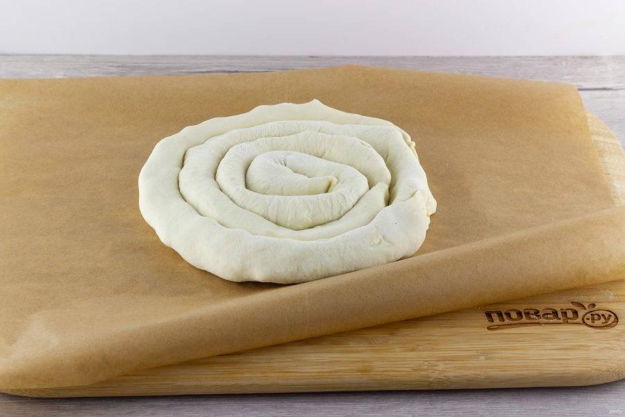 Выложите колбаски друг за другом в виде улитки на противень, застеленный бумагой для выпечки.