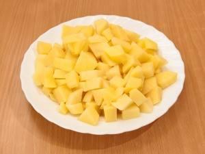 Нарежьте кубиками картофель.