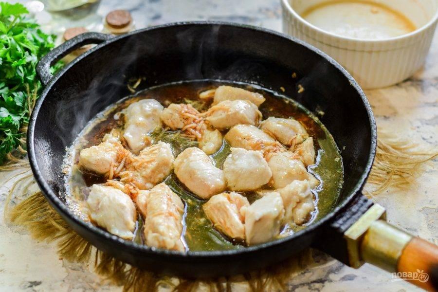 В сковороде прогрейте растительное масло, выложите кусочки курицы и поджарьте по две минуты с каждой стороны. Теперь добавьте в сковороду соус.