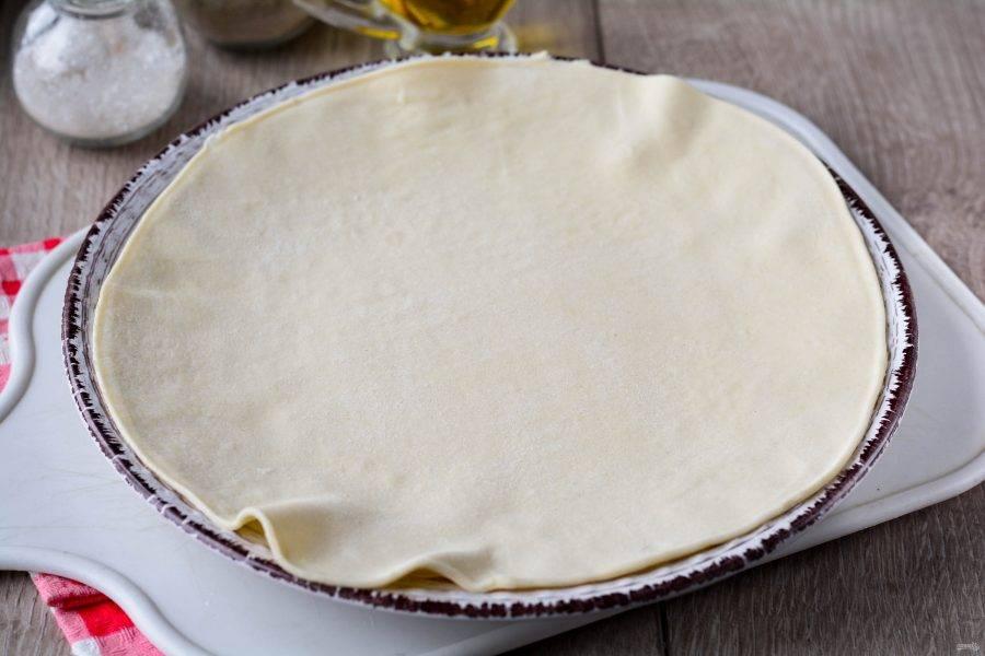 Раскатайте слоеное тесто в виде круга диаметром 20-22 см.