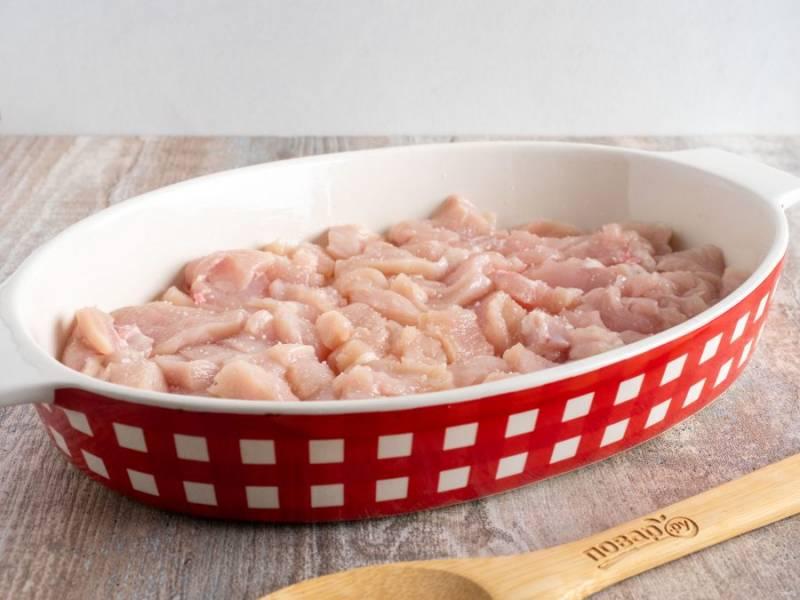 Форму для запекания смажьте растительным маслом. Филе курицы нарежьте небольшими пластинами. 2/3 курицы выложите на дно формы. Посолите и поперчите по вкусу.