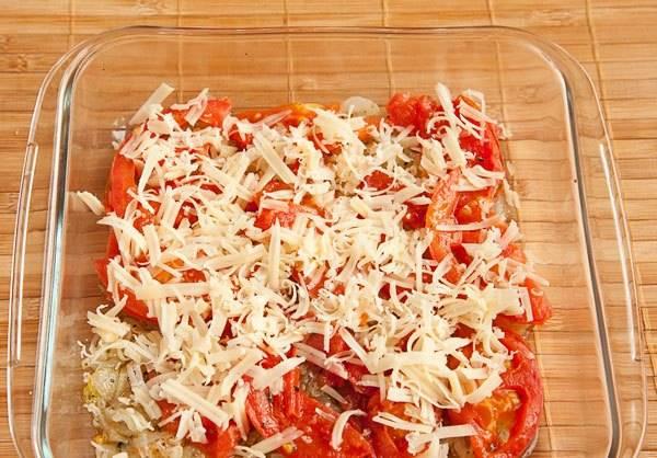 Кладем в форму для запекания лук, сверху помидоры. Присыпаем тертым сыром.