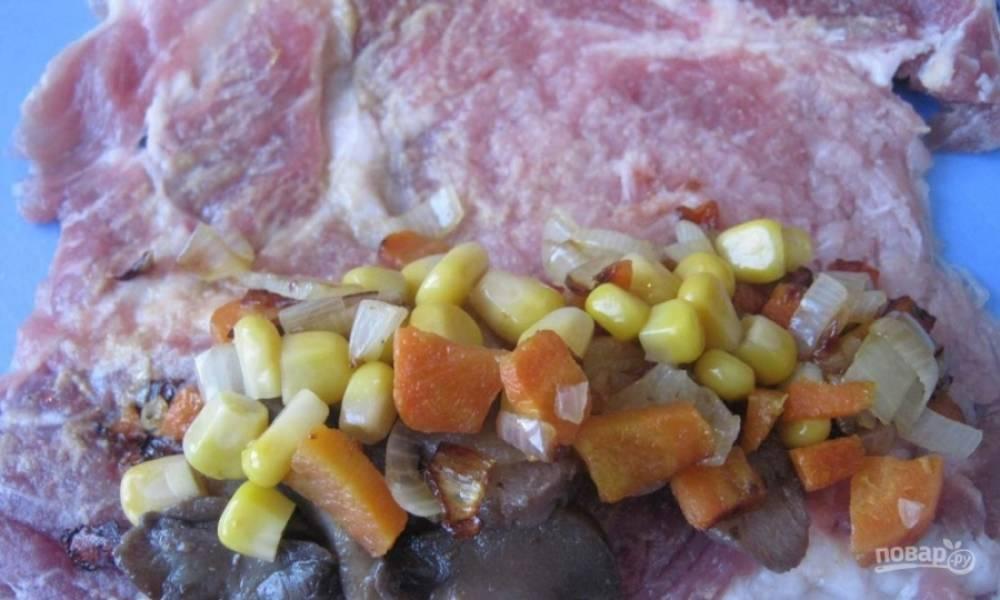 На один край отбитого и замаринованного в специях куска мяса выложите понемногу подготовленных шампиньонов, лука с морковью, а также консервированной кукурузы. Предварительно необходимо смазать горчицей эту сторону.
