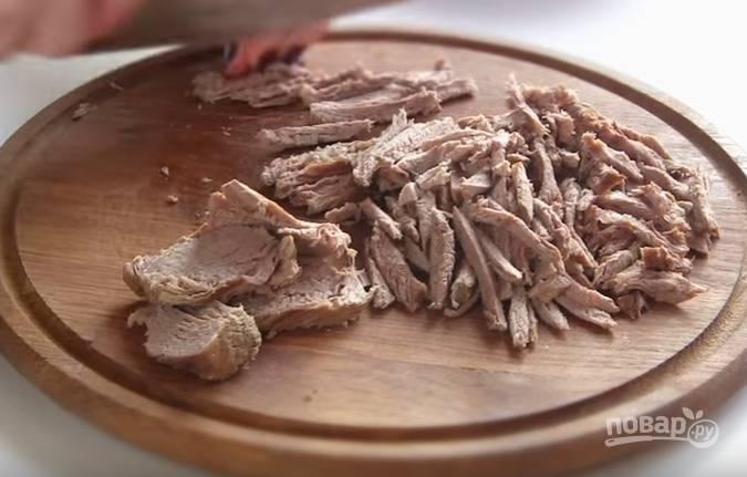 1. Отварите телятину в течение минут 40. Параллельно сварите яйца вкрутую и морковь до мягкости. Затем мясо остудите и нарежьте соломкой. Выложите на блюдо первым слоем. Смажьте майонезом.