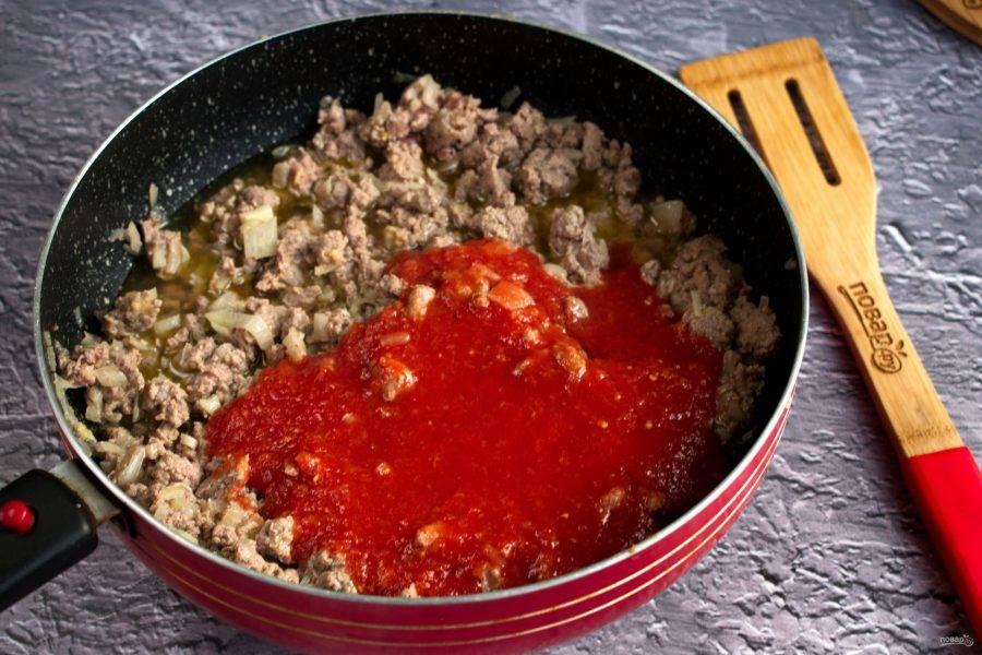 Добавьте томатное пюре, перемешайте. Тушите до испарения жидкости.