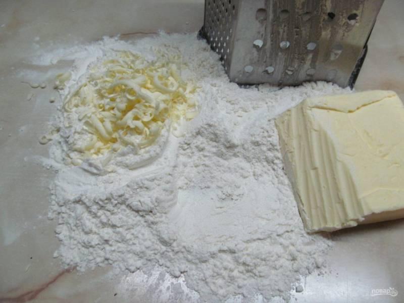 Еще для приготовления теста нужно заморозить сливочное масло. Высыпать муку на рабочую поверхность и начинаем натирать масло на крупную терку. При этом периодически перемешиваем масло с мукой и продолжаем натирать.