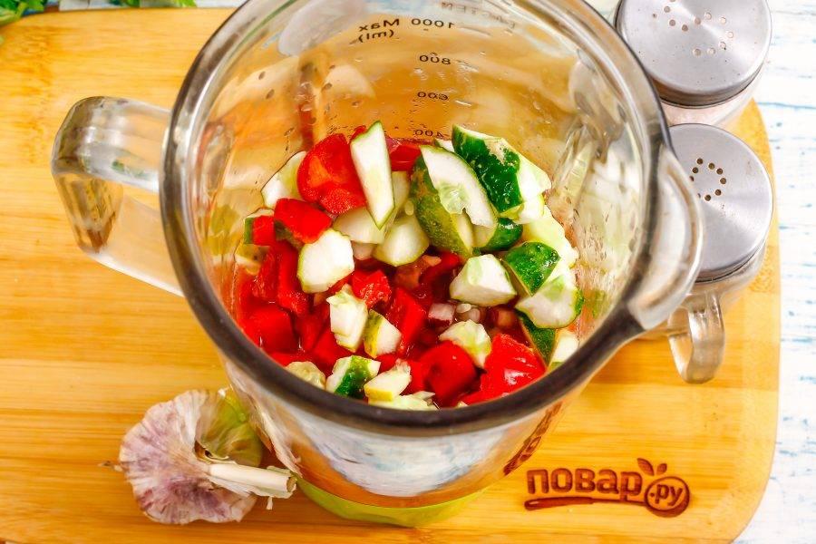 Влейте томатную массу в кувшин блендера, добавьте туда же пару очищенных зубчиков чеснока и все нарезанные овощи.