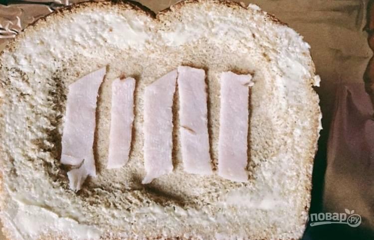 1. Тосты нарежьте на ломтики средней толщины, ложкой сделайте небольшую выемку в центре. Смажьте хлеб маслом   и уложите в центр несколько ломтиков ветчины.
