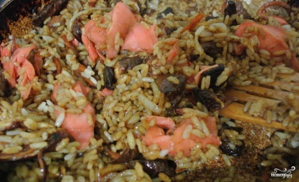 Сливаем остатки маринада, добавляем рис и маринованный имбирь. Перемешиваем и жарим блюдо до готовности.