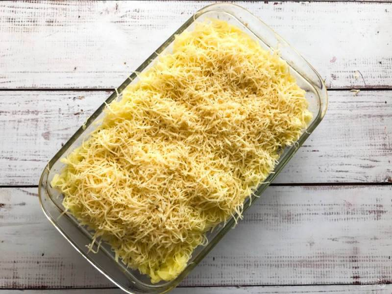 Поверх картофеля выложите тертый сыр и отправьте в предварительно разогретую до 180 градусов духовку на 30 минут.