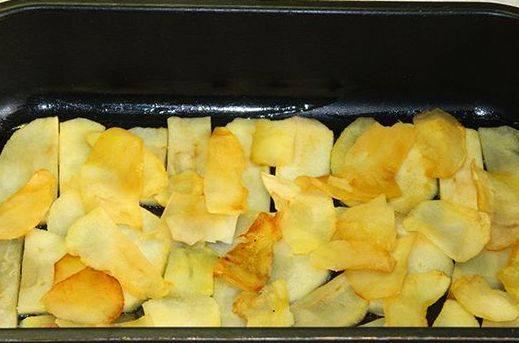 Теперь оставшимся сливочным маслом смазываем форму для запекания и выкладываем в нее ровным слоем обжаренные яблоки.