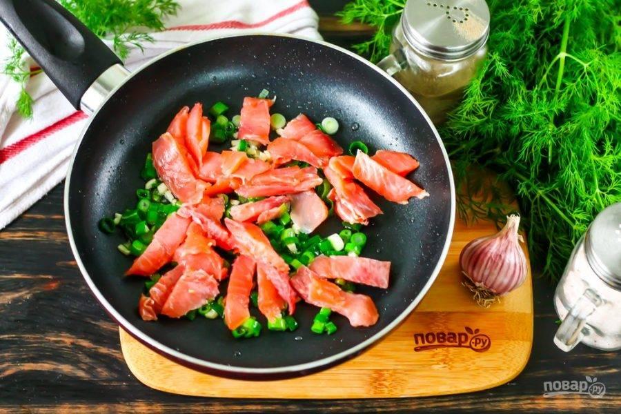 В это время нарежьте кусочками филе лосося, добавьте его на сковороду. Обжарьте около 2 минут, время от времени перемешивая.